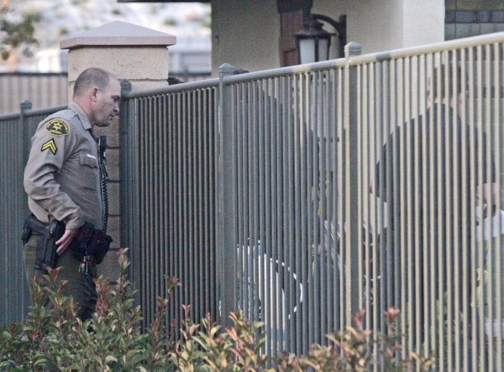 A sheriff's deputy looks through the fence around the pool and hot tub at River Village off of Newhall Ranch Road on Tuesday as paramedics perform CPR on a person who was found unresponsive. Katharine Lotze/Signal