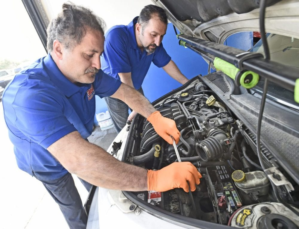 360 Auto Clinic Co-owners Armen Fanoosian, left, and Serjik Ghahramanians, install a new battery in the 2002 Chryser PT Cruiser they will be giving a way to a worthy person on December 22nd 2016 in Valencia.e car. Dan Watson/The Signal