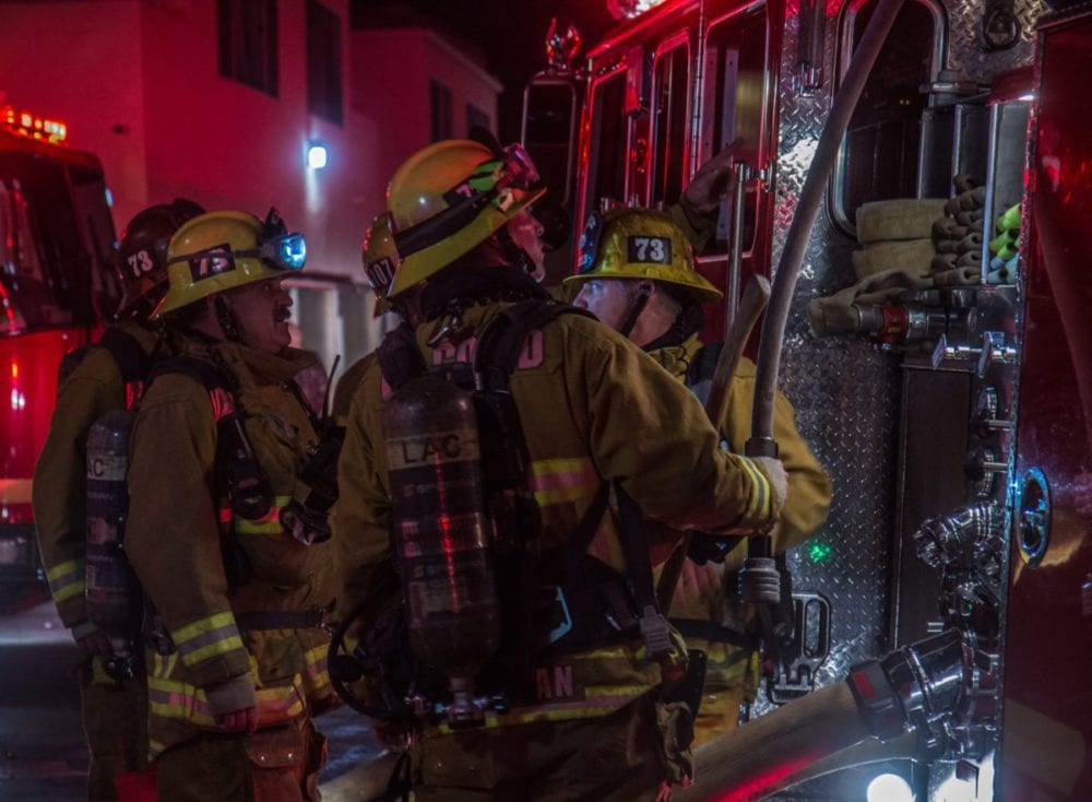 Firefighters form a plan near Fire Engine No. 107 at the scene of an apartment blaze. Austin Dave/SIGNAL