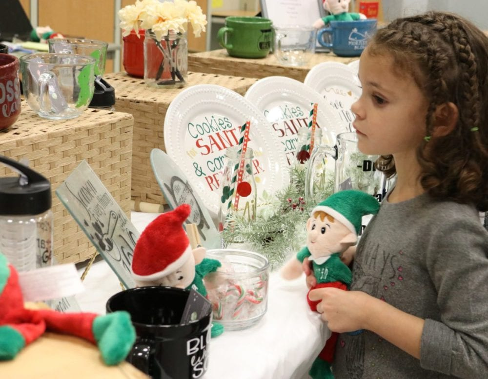 Savannah Denuccio, 6, looks at the homemade crafts for sale at the Brooklyn's Blessing Boutique and Toy Drive at Placerita Junior High School in Newhall on Sunday. Nikolas Samuels/The Signal