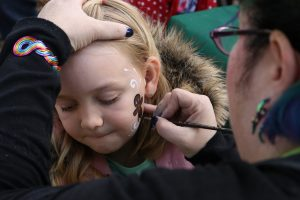 Riley Gibbs, 8, gets her face painted during Holiday Santa Day at Carousel Ranch in Santa Clarita on Saturday. Nikolas Samuels/The Signal
