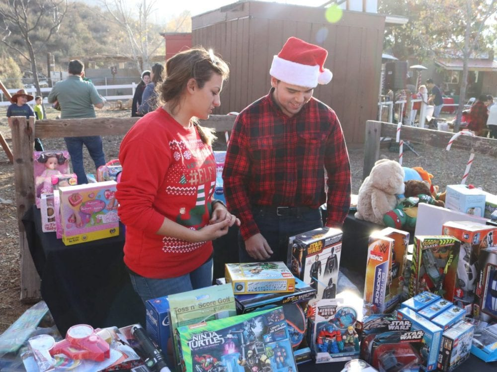 Janessa Yancy, left, and Brandon Ratner hand out presents to the children at Holiday Santa Day at Carousel Ranch in Santa Clarita on Saturday, Dec. 10, 2016. Nikolas Samuels/The Signal