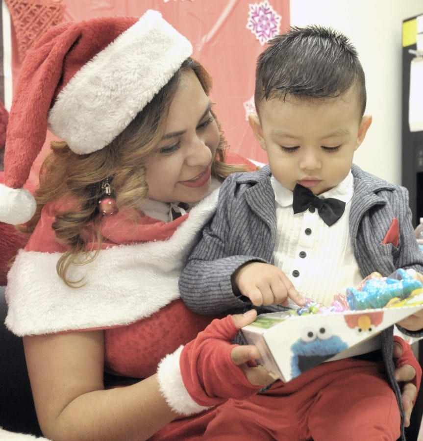 Patricia Quinteros, left, as Mrs. Santa Claus hands out an Elmo play set to Andrew Alas, 2, at the Santa Clarita Health Center in Canyon Country on Friday.  Dan Watson/The Signal