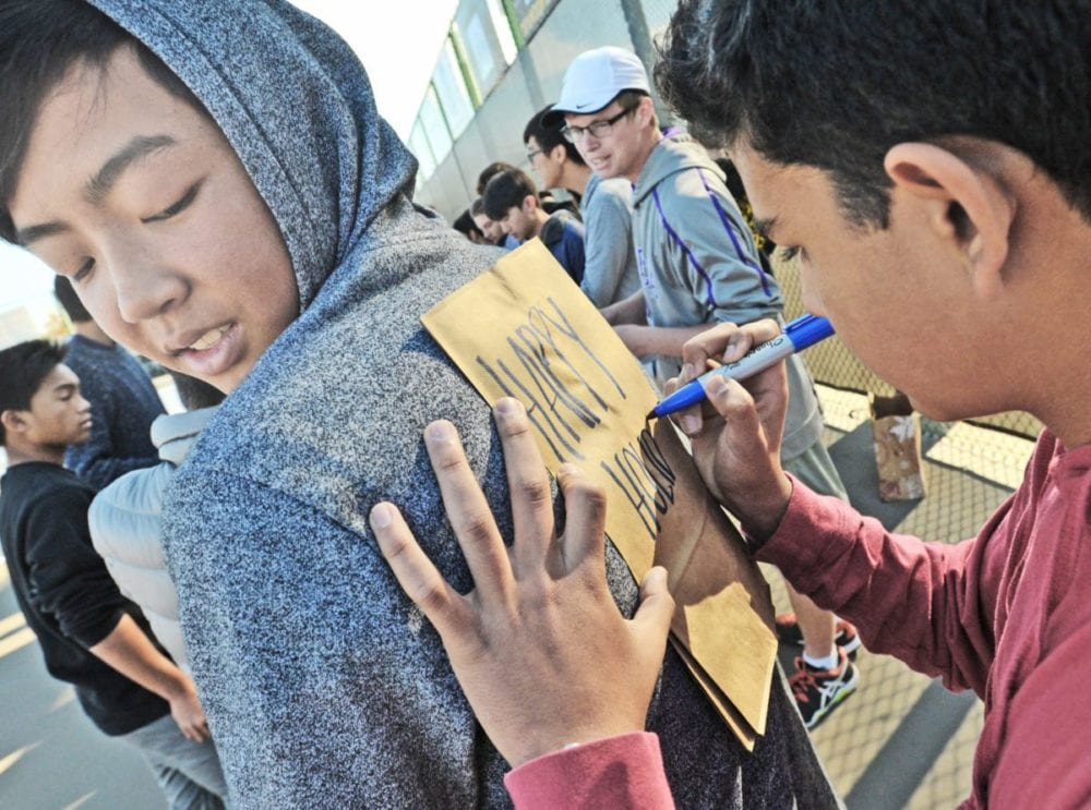 """Shantanu Jhaveri (cq), right, uses Stephen Thay back as Jhaveri writes """"Happy Holidays"""" on one of the paper bags that the Valencia boys tennis team used to create 60 bag lunches for Bridge To Home on Thursday. Dan Watson/The Signal"""