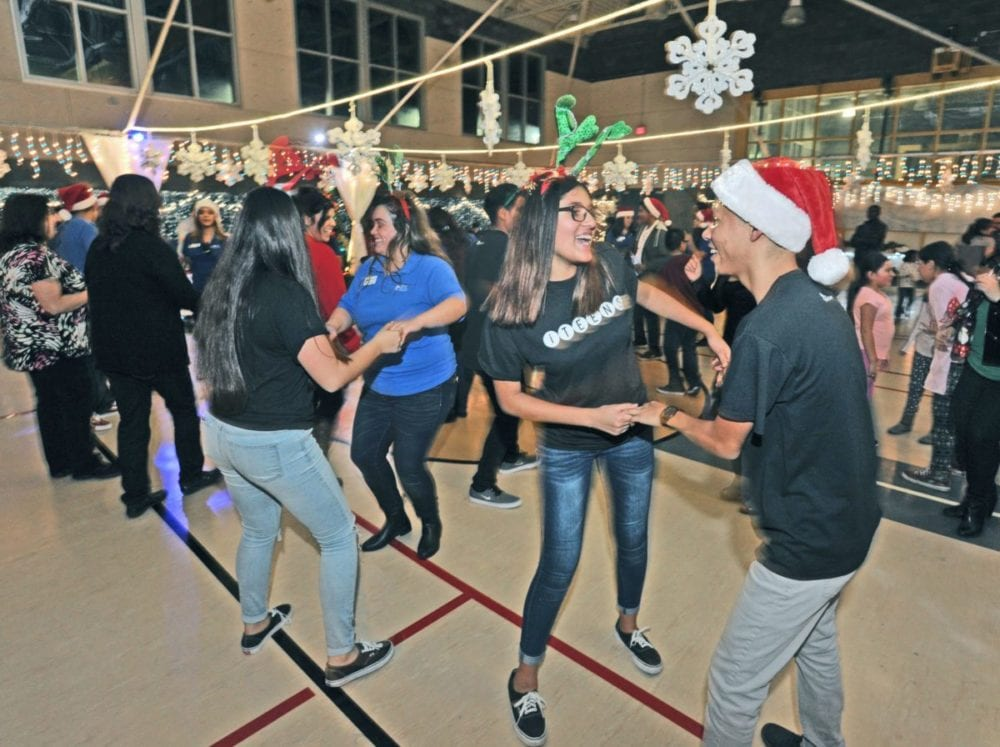 Dozens of attendees dance to the DJ's music at the at the Newhall Community Center's Holiday Family Party in Newhall on Friday. Dan Watson/the Signal