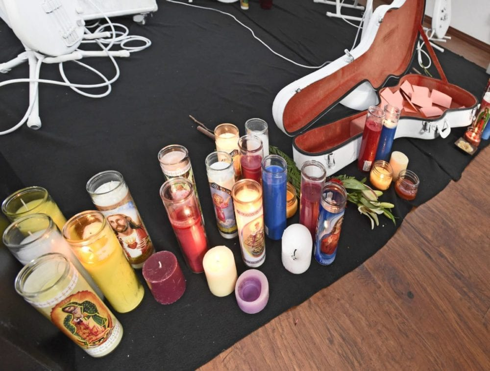 """Lit candles stand near an open guitar case as part of the art work """"Ghost Band"""" on display at the ARTree studio in Newhall on Saturday. """"Ghost Band"""" is an altar for musicians which was modeled after roadside displays where individuals have been killed while biking. Attendees are encouraged to write a note to musicians who are missed and place the note in the open guitar case as a remembrance of them. Dan Watson/The Signal"""