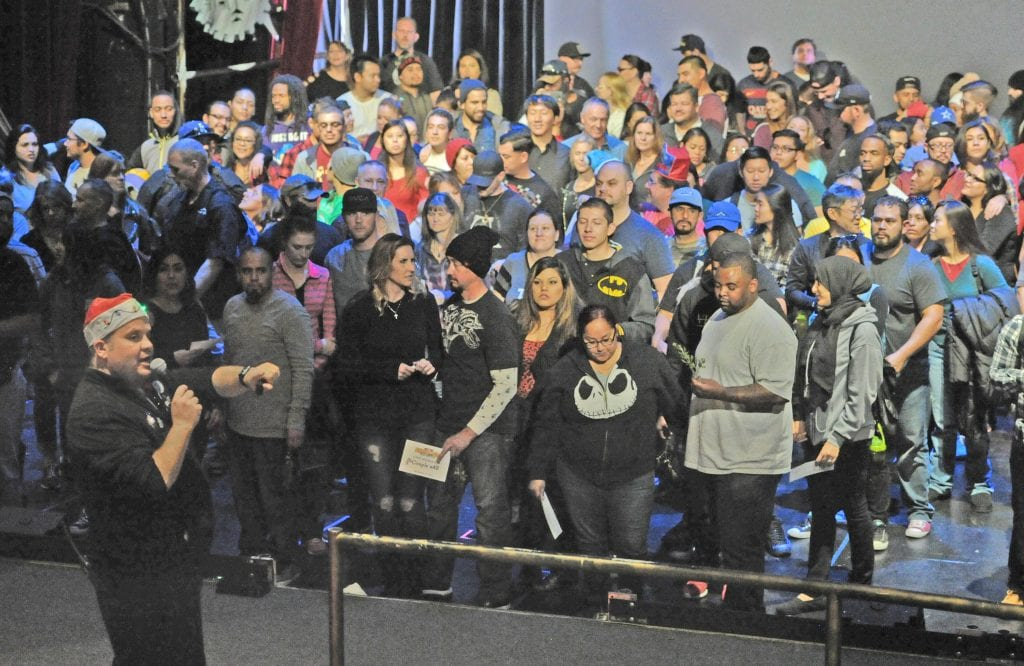Group Sales Manager Gavin Grozier, left, points to the exit after the more than 100 couples gathered on stage at the Gearworks Theater at Six Flags Magic Mountain in Valencia to participate the seven, Six Flags theme park attempt to break the Mistletoe Kiss Record on Saturday. Dan Watson/The Signal