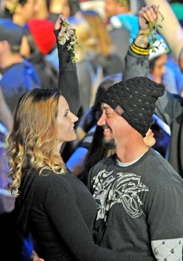 Mariann Corning,left, and Dan Redmond of Simi Valley hold up their mistletoe as they prepare to join more than 100 couples on stage who kissed for 12 seconds at the Gearworks Theater at Six Flags Magic Mountain in Valencia as they participate in a seven, Six Flags theme park attempt to break the Mistletoe Kiss Record on Saturday. Dan Watson/The Signal