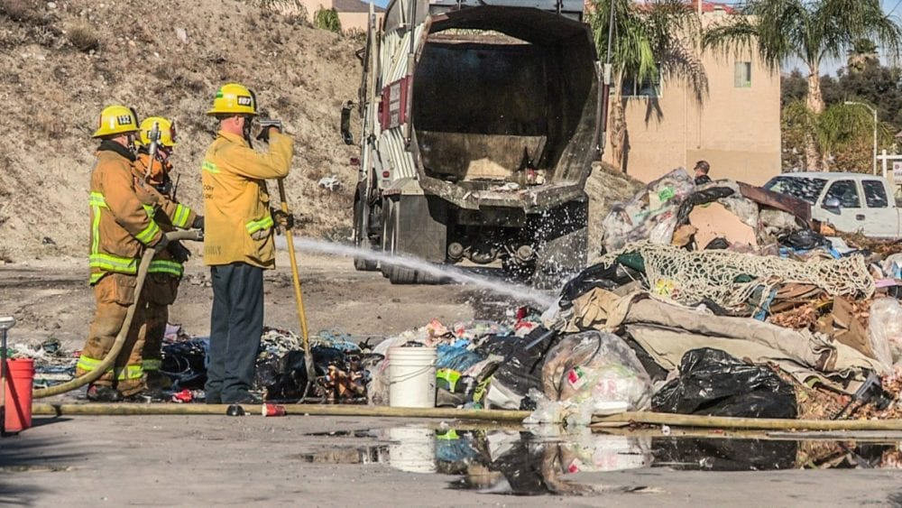 Firefighters apply water to a pile of burning garbage. photo by Austin Dave, The Signal.