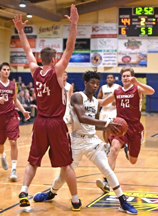 TMU's Lawrence Russell (2) gets past Westmont College Sam Bentz (42) and Jonathan Harrell (34) for a basket in the second half of the game. Photo by Jayne Kamin-Oncea/For The Signal