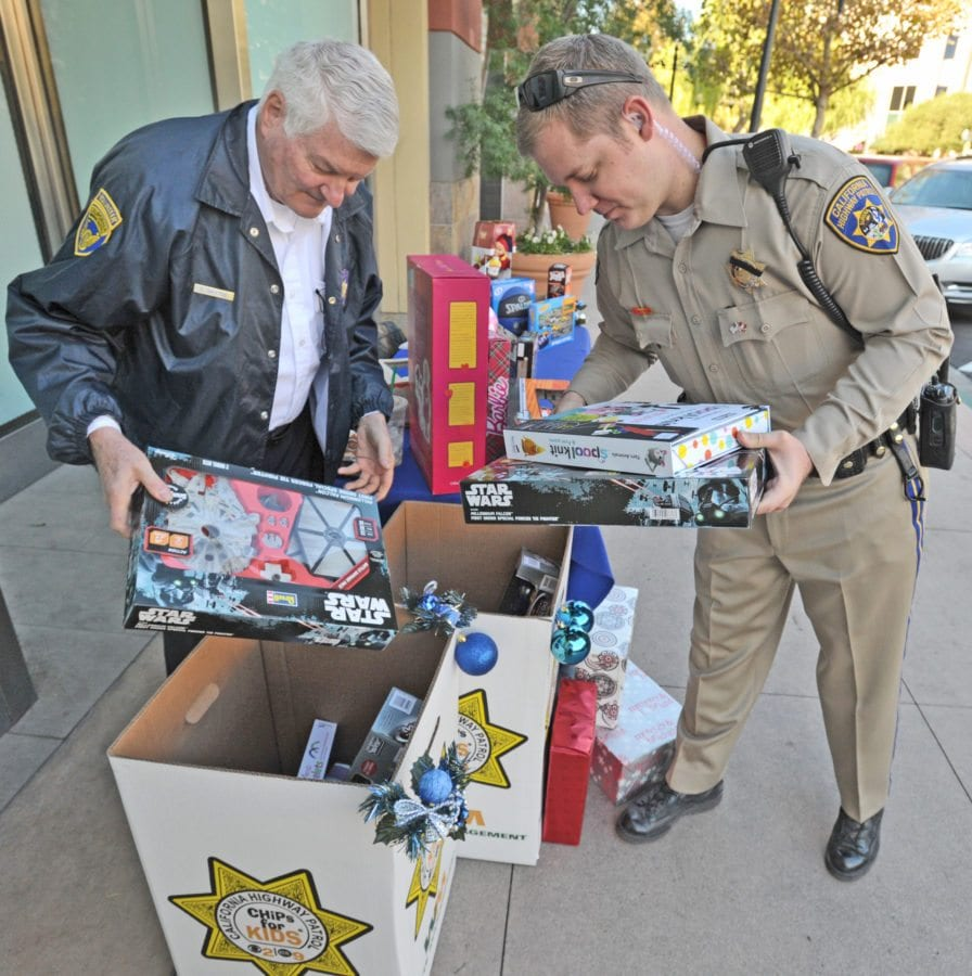 California Highway Patrol Senior Volunteer, Eugene Baxter, left, and CHP Officer Christian Stevens place donated toys in barrels at the CHP donation display on Town Center Drive in Valencia on Wednesday as part of the CHP's 28th year of collecting toys for local families in Santa Clarita. The CHP donation site will be accepting toys until December 15th at the location. Dan Watson/The Signal