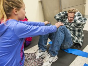 Newhall Elementary fifth grader Kiley Norman (L) holds her dad's ankles as he does a few sit ups during the Fifth Grade Health Night at the school. Photo Tom Cruze/For the Signal
