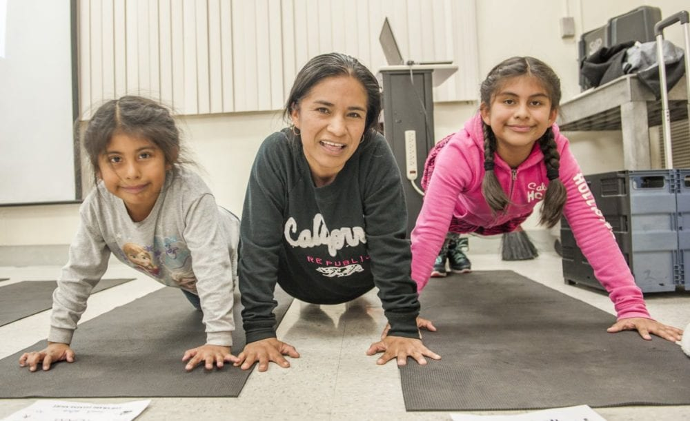 Newhall Elementary fifth grader Daniela Galindo (R) is joined by her sister Genisis (L) and her mom Dora Gaspar (C) as they make push-ups a family affair during the Fifth Grade Health Night at the school. Photo Tom Cruze/For the Signal