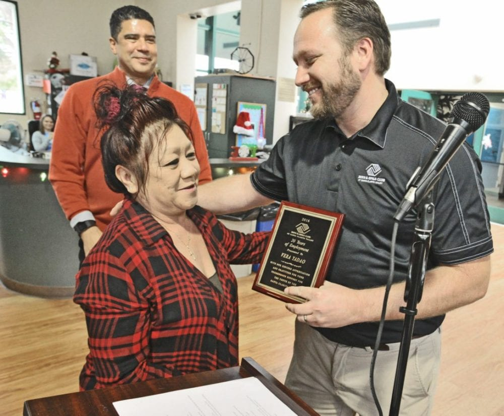 Boys & Girls Club of Santa Clarita Valley CEO David Menchaca, rear, looks on as Director of Operations Matt Nelson, right, presents Vera Yadao with and award for 20 years of employment at the Boys & Girls Club of Santa Clarita Valley 2016 Holiday Luncheon held at the Boys & Girls Club of Santa Clarita Valley in Newhall on Tuesday. Dan Watson/The Signal