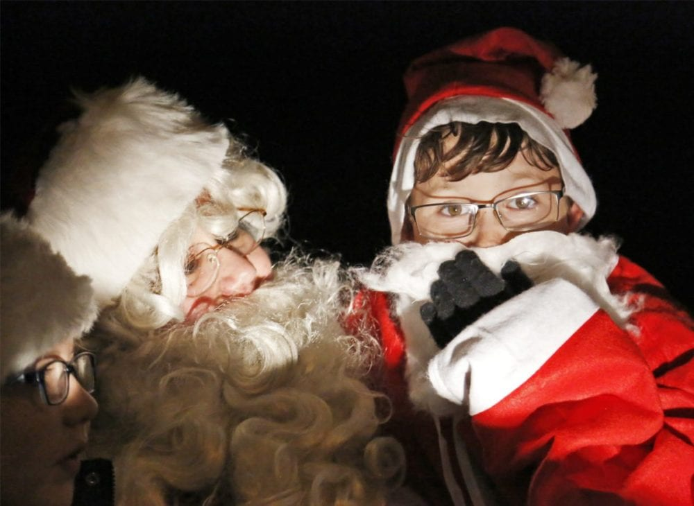 Joshua Davis, dressed as Santa Claus, visits with Santa Claus on the annual Lion's Club Santa Float in Castaic on Monday. Katharine Lotze/Signal