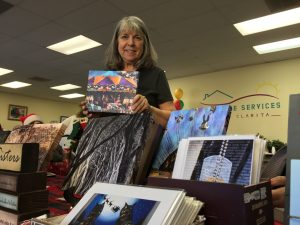 Norma Warden poses with her photography on Sunday at the Holiday Boutique at Home Care Services. Samie Gebers/ Signal