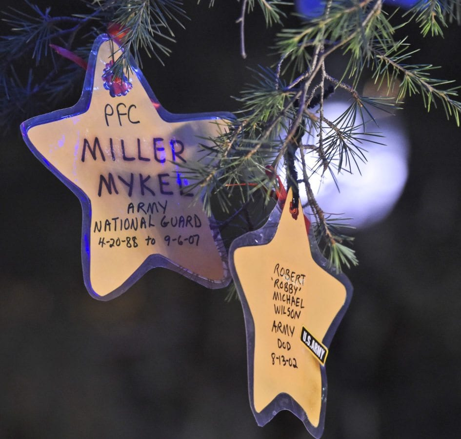 Ornaments bearing the names and photos of members of the military hang on the lighted tree at the 11th annual Military Tree Lighting at Veterans Historical Plaza in Newhall on Saturday. Dan Watson/The Signal
