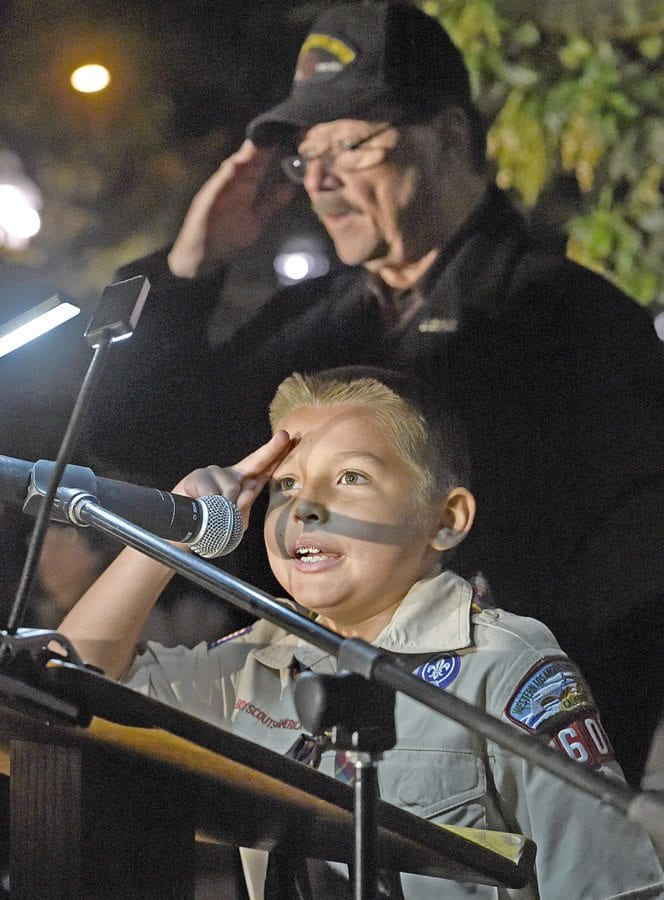 Boy Scout Justin Hamilton, 9, salutes with U.S. Marine veteran Dick Jeffrey as Hamilton leads the dozens of attendees in the Pledge of Allegiance at the 11th annual Military Tree Lighting at Veterans Historical Plaza in Newhall on Saturday.  Dan Watson/The Signal