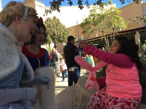 Lourdes Silva, left, shows her new toy to princesses on Saturday at the 6th Annual Combat Radio Christmas Event for Social Services. Samie Gebers/ Signal