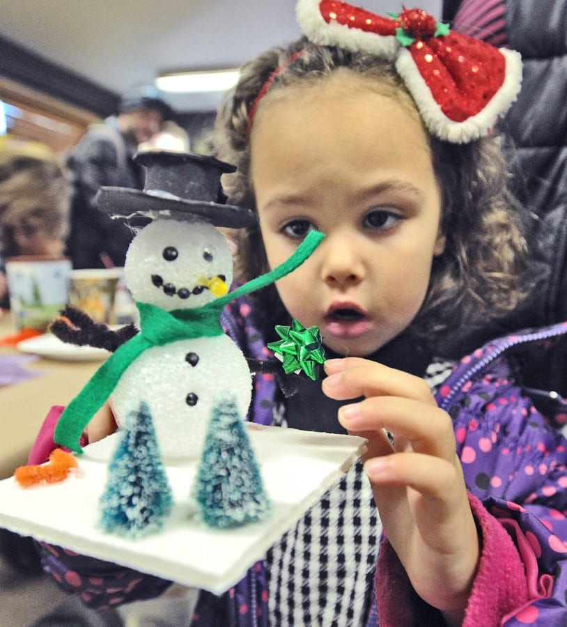 Daisy Collupy, 4, of Acton decorates her snowman, one of the craft stations for children and families at the annual Holiday Craft Fair on Saturday which has been held at the Placerita Canyon Nature Center for more than 35 years in Newhall. Dan Watson/The Signal