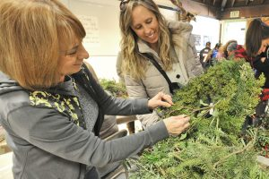 Kathie Hovore, left, and her daughter Holly create a wreath out of pine branches at the annual Holiday Craft Fair on Saturday. The two have attended the annual event for more than twenty years which has been held at the Placerita Canyon Nature Center in Newhall for more than 35 years. Dan Watson/The Signal