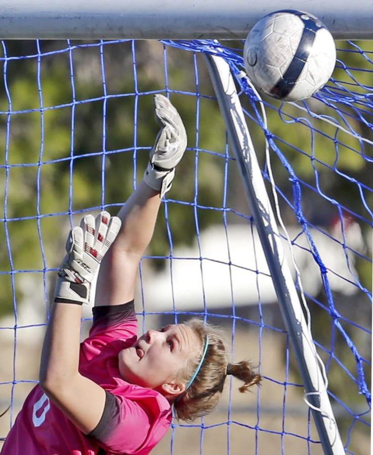 Saugus' goalkeeper Hailey Billesbach (0) jumps to block a corner kick from Oak Park during a varsity soccer game at Saugus on Friday. Katharine Lotze/Signal