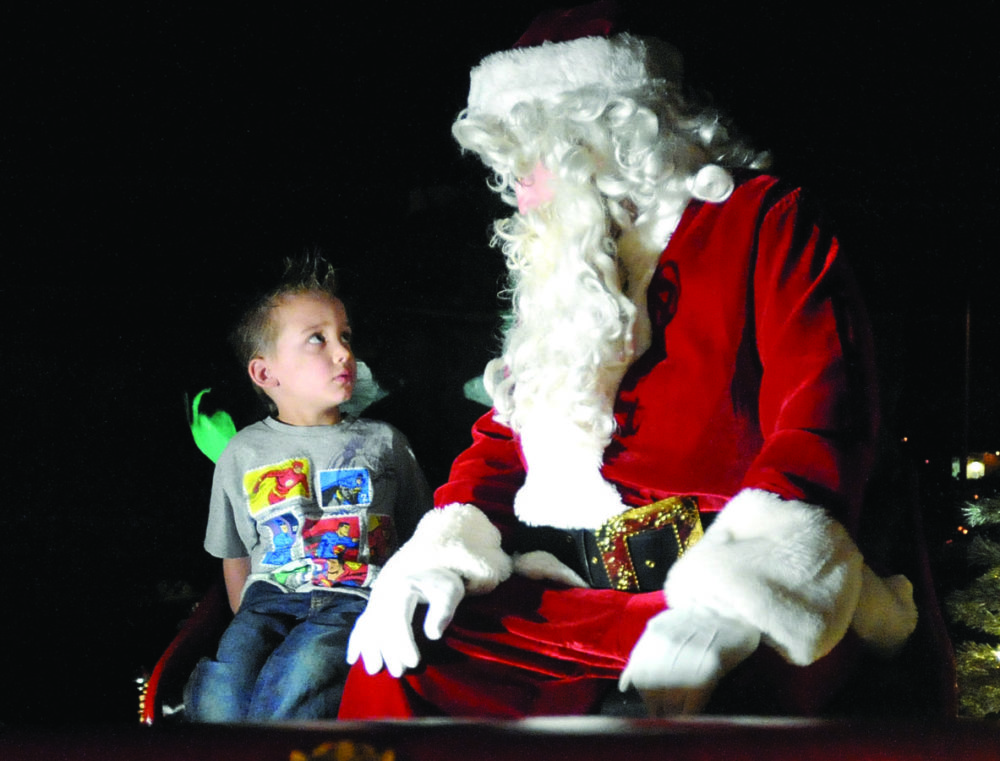 Jameson James-Yous, 4, visits with Santa on Monday night during the annual Castaic Santa Float. KATHARINE LOTZE/SIgnal. 12072015