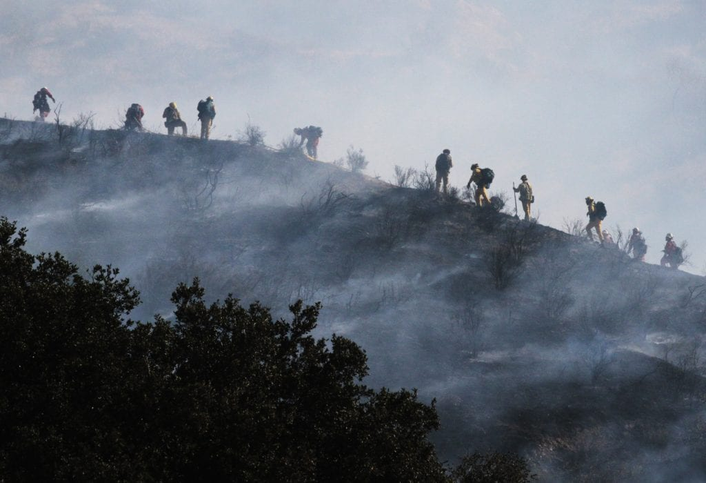 Fire crews work to put out hot spots on a ridge off of northbound Highway 14 in the Newhall pass on Friday. Katharine Lotze/Signal