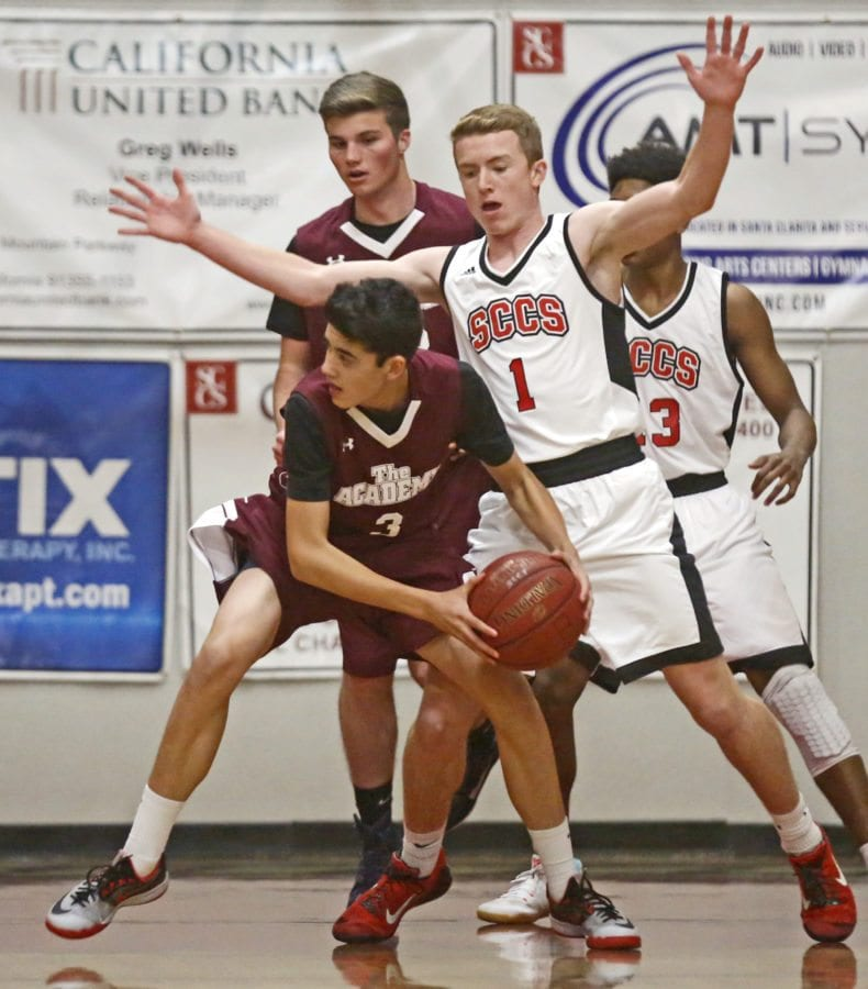 Albert Einstein Academy's Brandon Cove (3) looks for a pass as SCCS' Tyler Kalinske (1) tries to block him during a basketball game at SCCS on Thursday. Katharine Lotze/Signal
