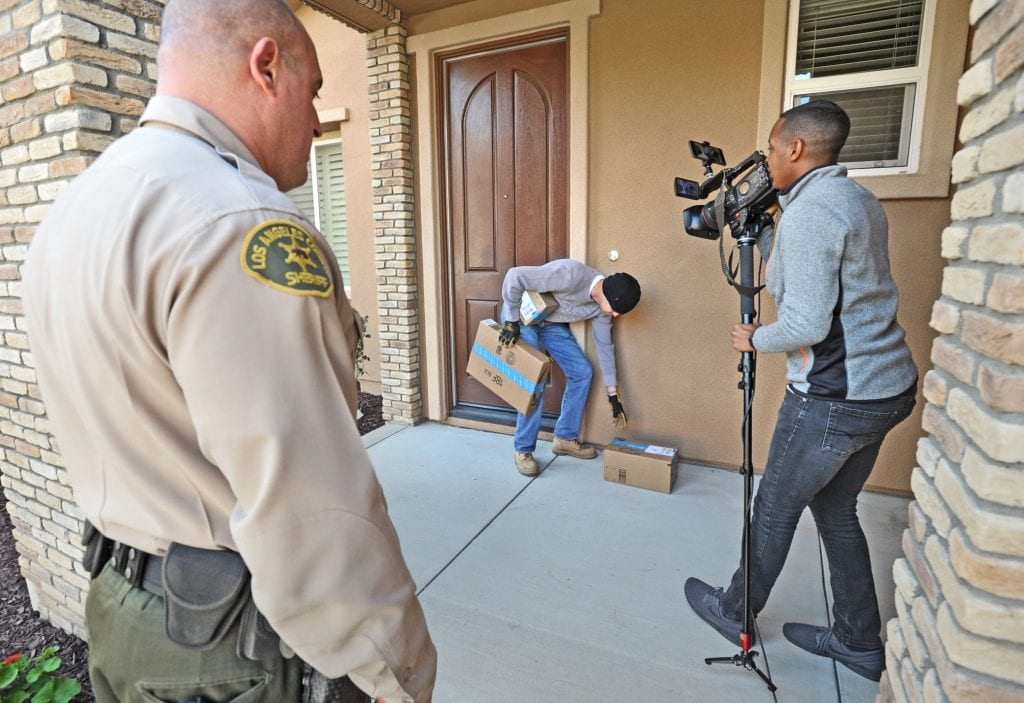 The Signal Chief of Video Austin Dave, right, video tapes a Mannequin Challenge scenario where a person portrayed by Santa Clarita Sheriff's Deputy Kevin Duxbury steals delivered packages from a doorstep as Sheriff's Deputy Brian Heischuber, left, looks on in Saugus on Thursday as they film a Sheriff's Department to remind people of how to protect themselves from theft during the holidays. Dan Watson/The Signal