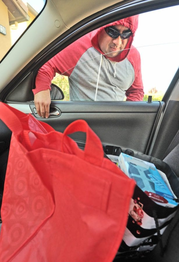 Santa Clarita Sheriff's Deputy Luis Cabrera portrays a person stealing shopping bags from an unlocked car in a driveway in Saugus on Thursday as he participates in a Sheriff's Department Mannequin Challenge video to remind people of how to protect themselves from theft during the holidays. Dan Watson/The Signal