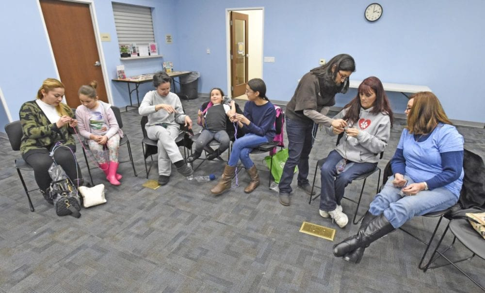 Instructor Nicole Ramirez, standing, demonstrates how to crochet a chain for a group of beginners during the Stitch it Together, crocheting class held at the Canyon Country Jo Anne Darcy Library on Saturday. Dan Watson/the Signal