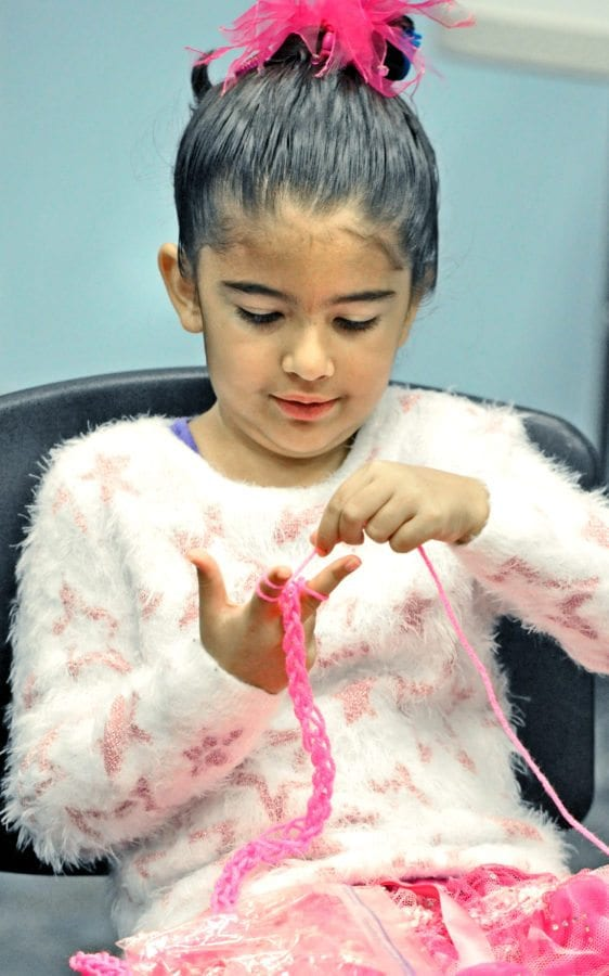 Lucila Anderson,7, learns to finger-knit a necklace during the Stitch it Together, beginning crocheting class held at the Canyon Country Jo Anne Darcy Library in Canyon County on Saturday. Dan Watson/the Signal