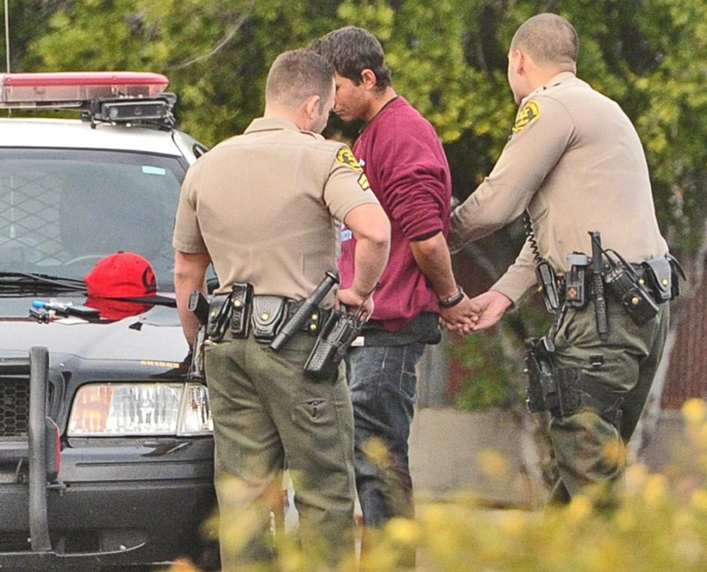 Santa Clarita Sheriff's Deputies detain a third man at the scene of a narcotics bust in the parking lot of the Jack in the Box restaurant at the corner of Crossglade Avenue and Soledad Canyon road in Canyon Country on Saturday. Dan Watson/The Signal