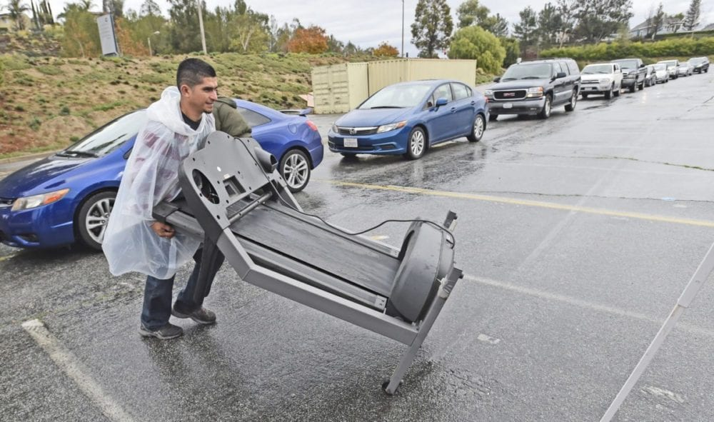 Worker Oscar Alvarez moves an electric tread-mill machine from a car in the long line if vehicles waiting to drop off old electronics for recycling at the e-waste recycling event hosted by William S. Hart High School at College of the Canyons in Valencia on Saturday. Dan Watson/The Signal
