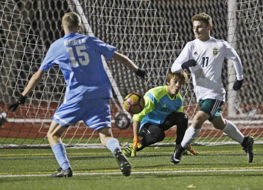 Canyon's Dylon Hartigan (11) kicks the ball away from the Cowboy's goal as goalkeeper Chase Moynihan (0) tries to recover during a soccer game against Quartz Hill at Canyon on Friday. Katharine Lotze/The Signal