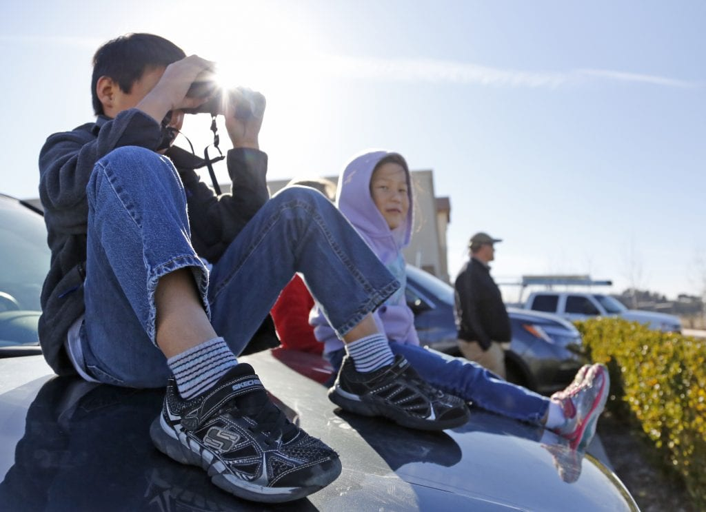 Cameron Paul, 7, looks through binoculars while sitting on the hood of his mom's car in the Lowes parking lot in Canyon Country with sister, Katie, 5, as they wait for several Apache helicopters to fly over the Santa Clarita Valley on Friday, Jan. 6, 2017. Katharine Lotze/Signal