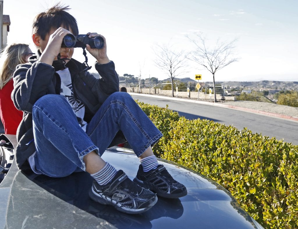 Cameron Paul, 7, looks through binoculars while sitting on the hood of his mom's car in the Lowes parking lot in Canyon Country as he and mom, Karin and sister Katie, 5, wait for several Apache helicopters to fly over the Santa Clarita Valley on Friday, Jan. 6, 2017. Katharine Lotze/Signal