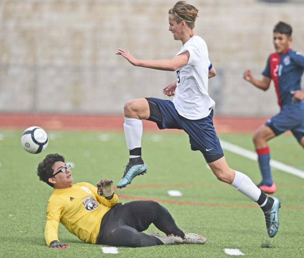 Saugus forward James Johnson (9) runs over Lancaster goal keeper Darwin Chavez to make a shot on goal in the first half at Saugus High School on Tuesday. Dan Watson/The Signal