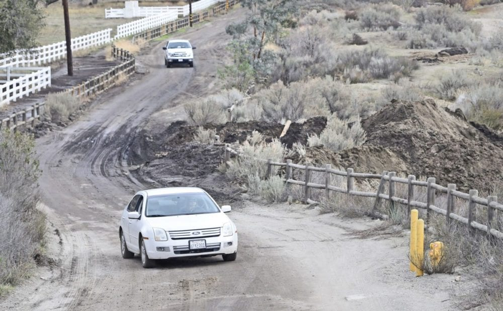 Residents pass through a muddy section of Oak Spring Canyon Road on Wednesday where a dirt berm, right, has been built next to Robinson Ranch Golf course to keep water, debris and silt from washing onto the golf course from the road. Dan Watson/The Signal