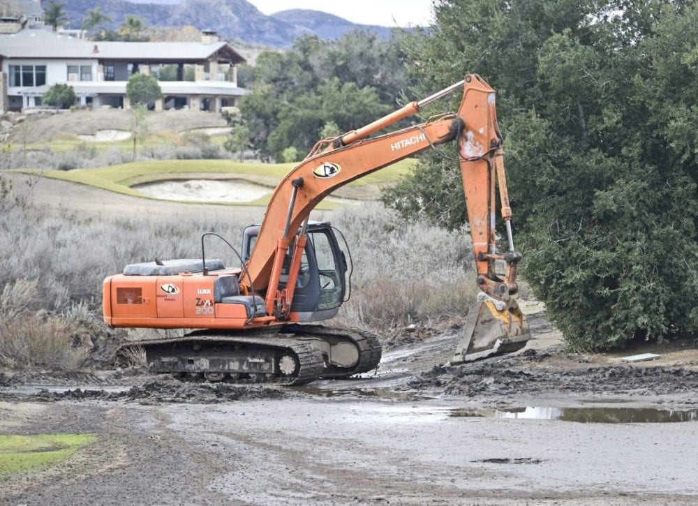 An excavator clears debris from Robinson Ranch Golf course near Oak Spring Canyon Road on Wednesday. Dan Watson/The Signal