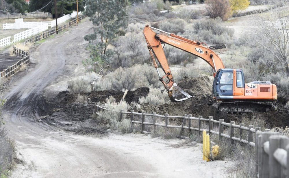 An excavator builds a berm along a muddy section of Oak Spring Canyon Road on Wednesday where a dirt berm has been built next to Robinson Ranch Golf course to keep water, debris and silt from washing onto the golf course from the road. Dan Watson/The Signal