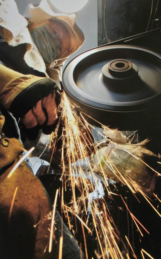 Sparks fly as Bill Herndon shapes a blade using one of six grades of sandpaper on a grinding wheel. Dan Watson