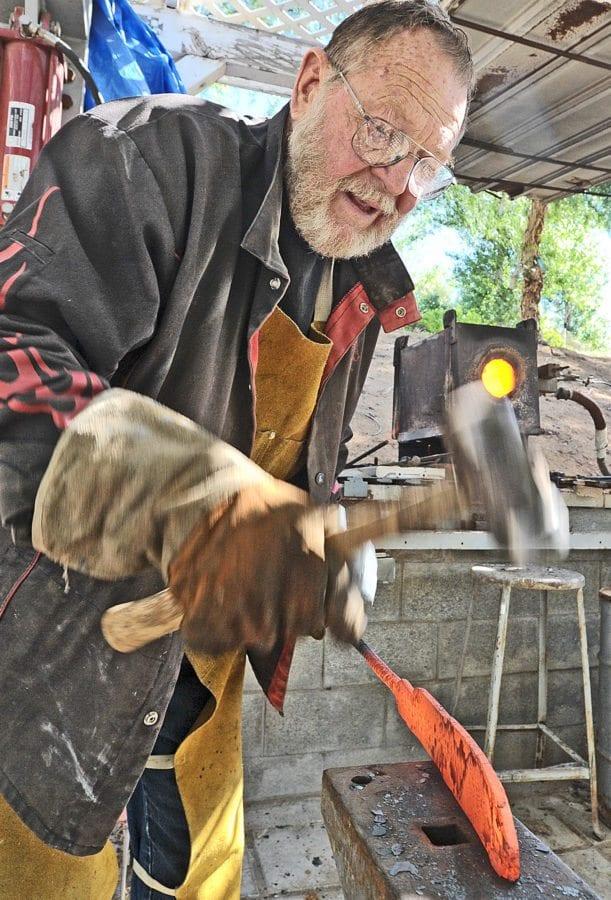 Bill Herndon uses a hammer on a hot steel blank to shape it into a blade. Dan Watson