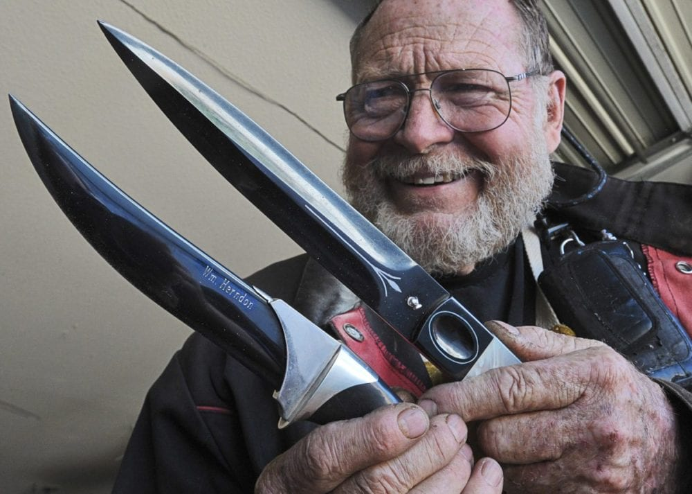 Bill Herndon displays two of his high art knives which would command more than $2,000 dollars each. The Persian style dagger on the left, has his name engraved in the blade and five ounces of silver, the knife on the right has silver inlay and mother of pearl handles. Dan Watson