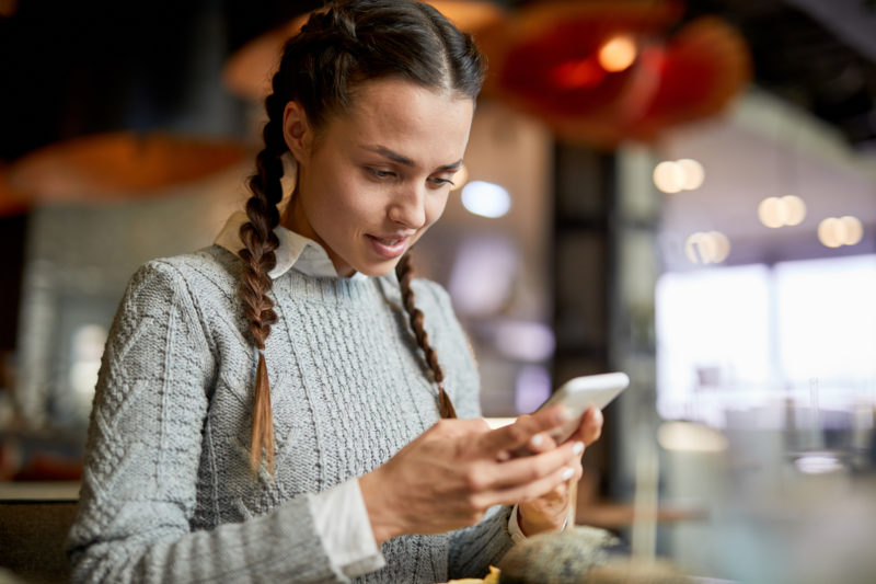 Brunette girl in light grey knitted sweater reading message in smartphone while spending time in cafe
