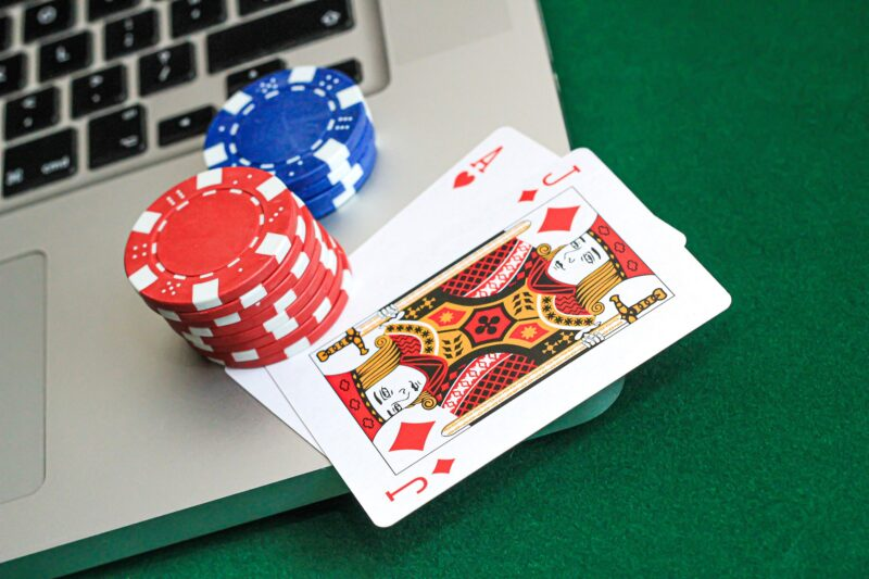 poker chips and cards on top of a laptop keyboard